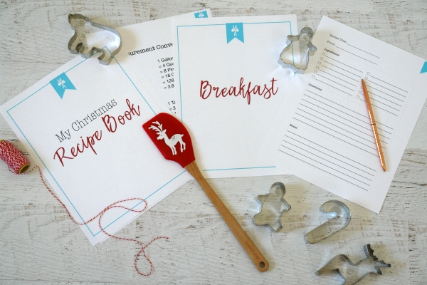 Christmas recipe book pages on white table with cookie cutters and spatula
