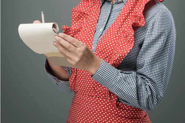 woman in apron writing list