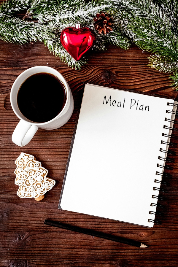 """notebook that says """"meal plan"""" with coffee and christmas cookie and decor on table"""