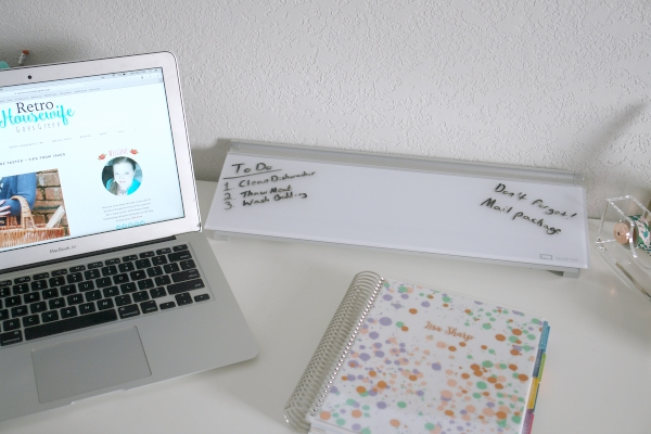 desk with laptop, planner and dry-erase pad
