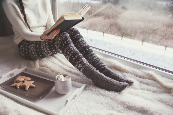 woman on window seat with cozy blanket and tray with hot chocolate, reading a book