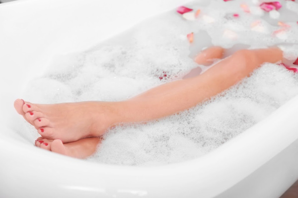 Woman legs with flower petals in bathtub with bubbles