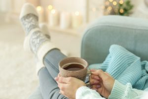 woman in cozy socks on sofa with cup of tea