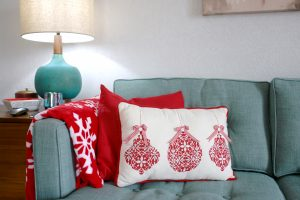 turquoise sofa with red Christmas pillows and blanket
