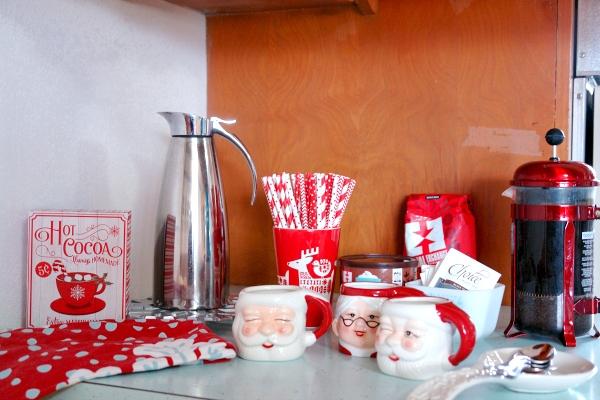 Christmas drink station with Santa mugs, coffee, pitcher, paper straws, a hot cocoa sign and more.