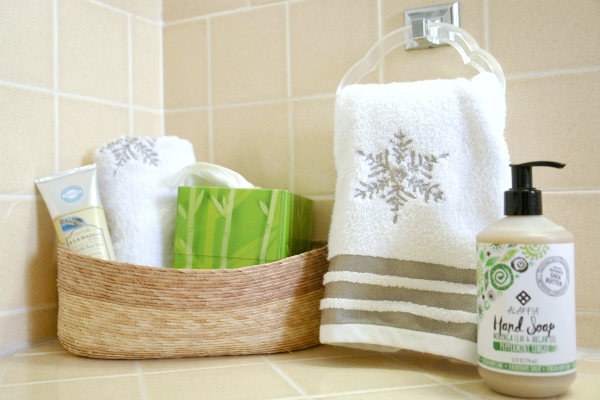 A bathroom countertop with snowflake hand towel and soap and a basket with extra supplies
