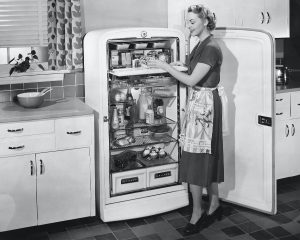 1950s housewife in front of open fridge