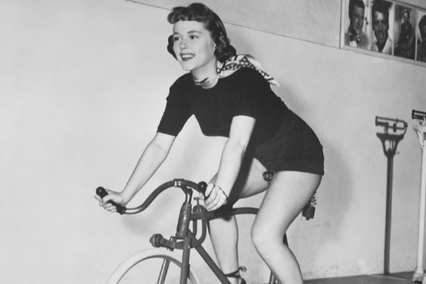 1950s housewife riding an exercise bike in the gym