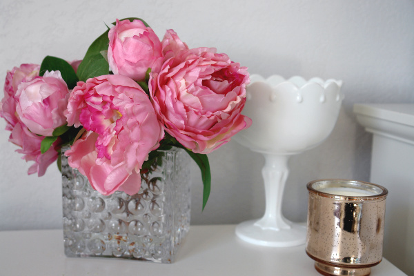 pink peonies in glass vase with milk glass and rose gold candle