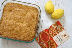 lemon coffee cake next to two lemons and 1950s cookbook