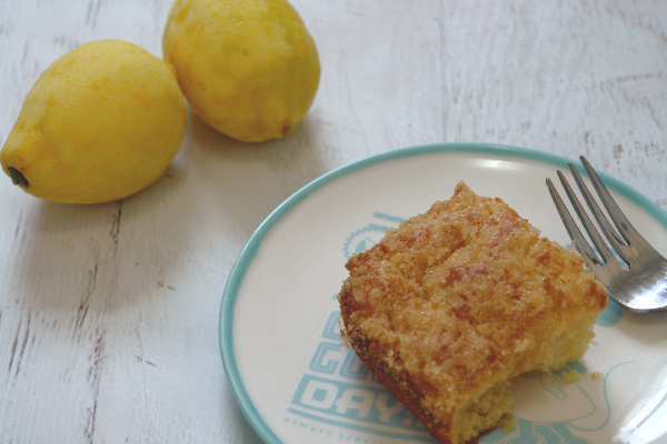 piece of lemon coffee cake on plate next to lemons