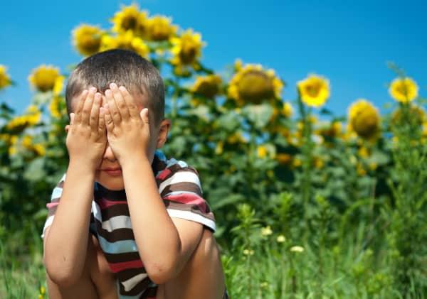 kid playing hide and seek outside