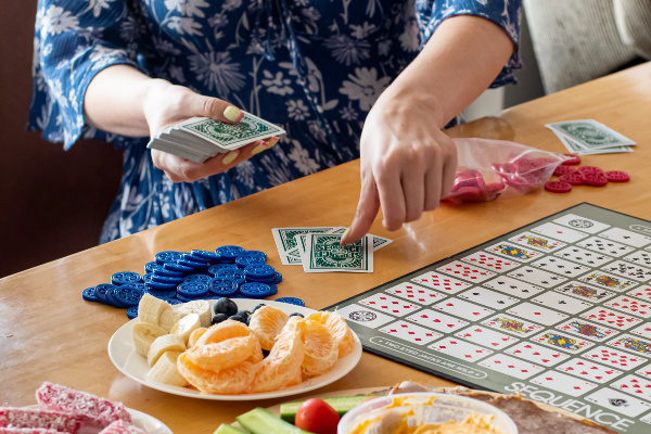 person dealing cards on table with snacks