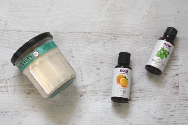 candle and essential oils on white table
