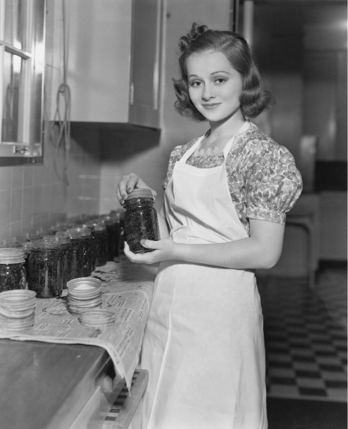 black and white photo of vintage housewife holding a jar she canned with more in the background