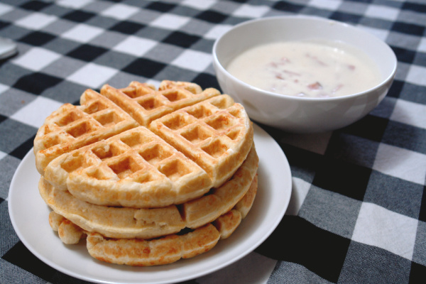 stack of cheese waffles and bowl of creamed ham on table