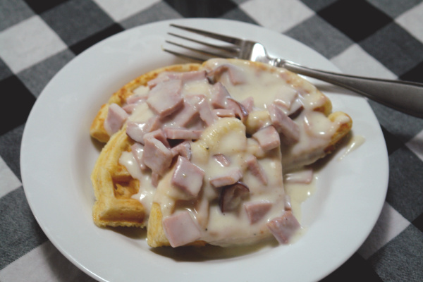 waffles on plate with creamed ham and fork