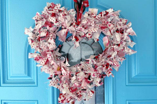 red, white, and pink valentines day rag wreath on blue door