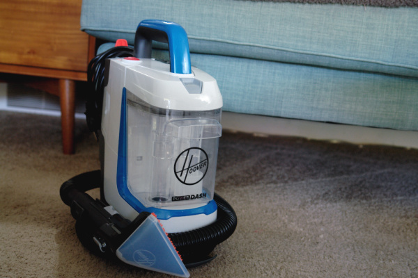 Hoover PowerDash GO Portable Spot Cleaner in front of sofa and end table