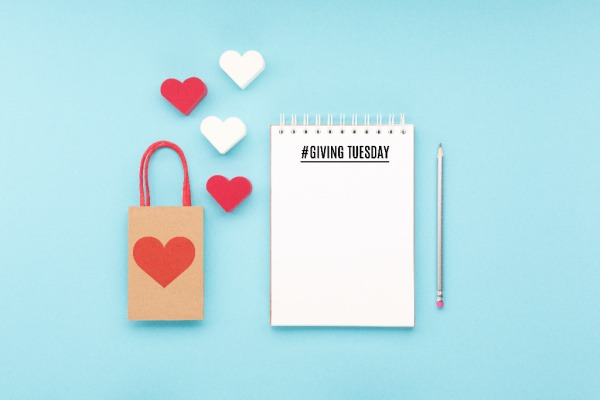 notepad that says giving tuesday, red heart and shopping bag on blue background.