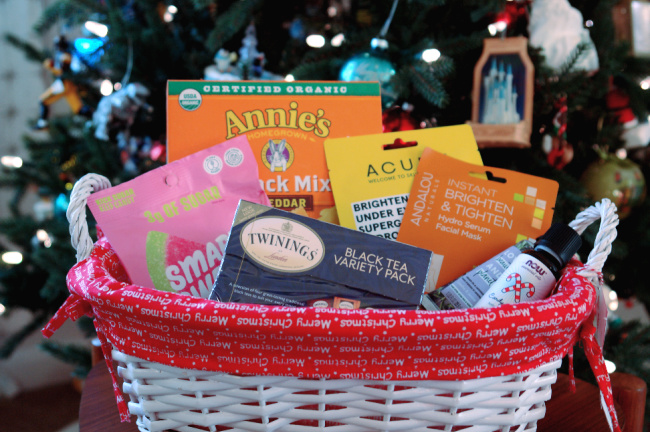snacks and beauty items in basket in front of christmas tree