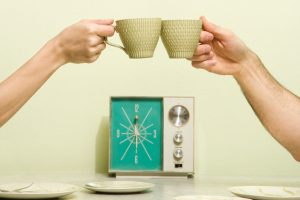 people clinking mugs in front of mid-century clock