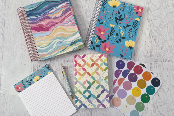 Erin Condren planner, notebooks, notepad, and stickers on white wooden table