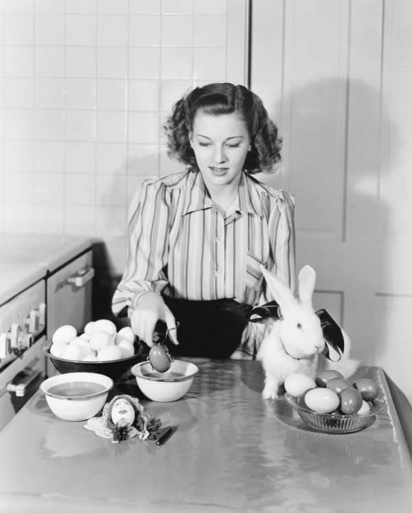 vintage housewife dying easter eggs with bunny sitting on table