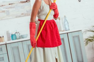 woman in yellow dress and heels with red apron holding mop