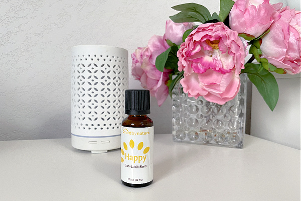 essential oil bottle in front of diffuser and pink flowers