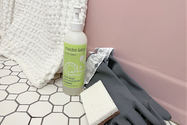 bottle of Madre Labs dish soap on tile floor next to pink bathtub, cleaning gloves, and sponges