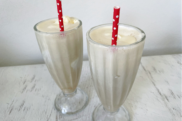 two vintage soda glasses filled with coffee floats with red polka dot straws