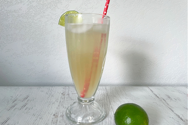 limeade in retro glass with red polka straw and a lime next to it