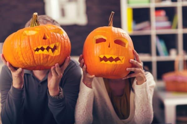 couple holding jack-o-lanterns over faces